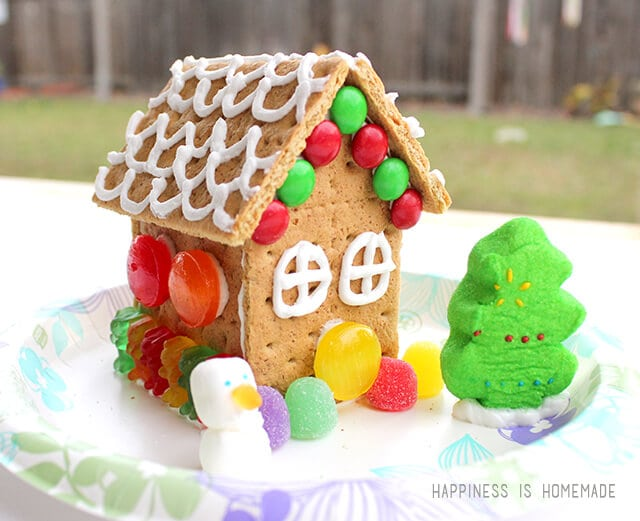 The graham crackers held together very well and the gingerbread houses came together quickly. I started with a basic box, added the triangle as a resting place for the eaves of the roof, and then added the roof.