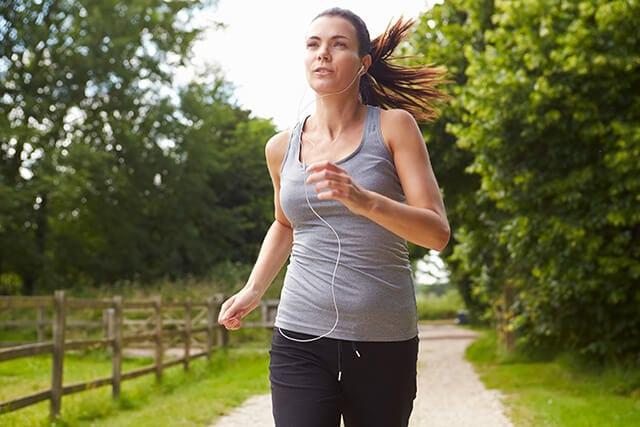 Woman Running In Countryside Wearing Earphones