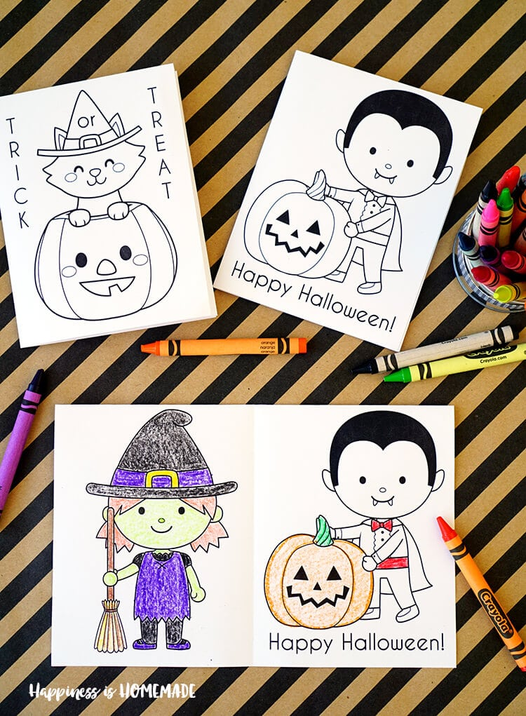 Cute Halloween Coloring Books on striped background with crayons