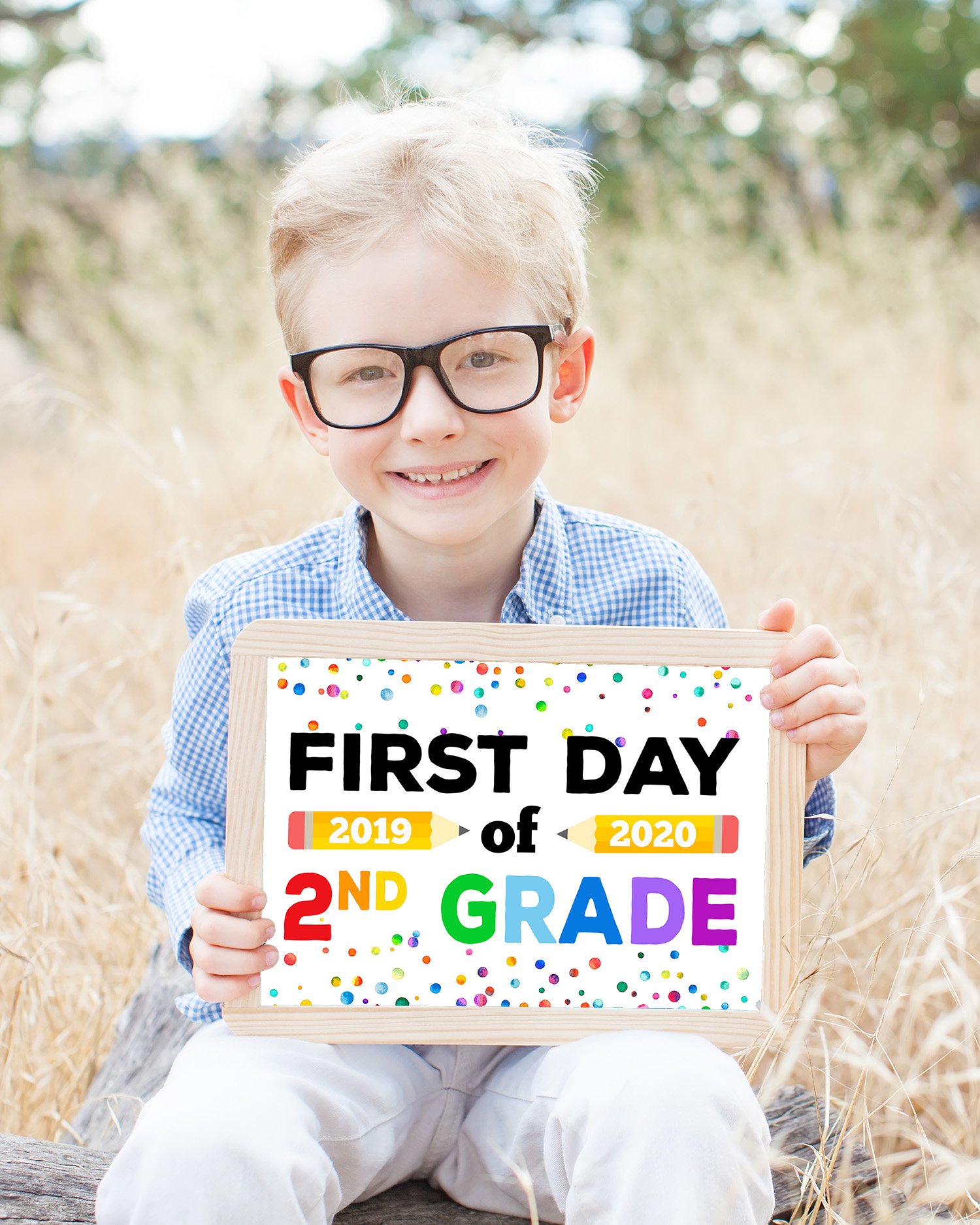 "Free Printable Back to School Signs - cute boy in glasses holding ""First Day of Second Grade"" sign"