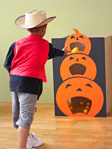use posterboard and a cardboard box to create this fun diy pumpkin toss game and see who can get the most ping pong balls into the jack olanterns mouth