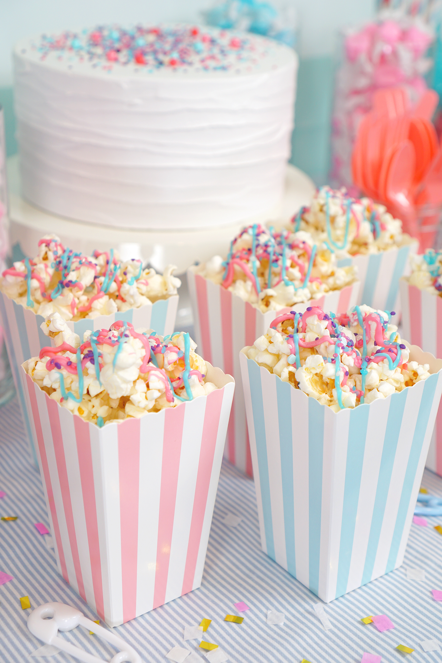 Pink and blue striped popcorn boxes filled with pink and blue drizzled popcorn