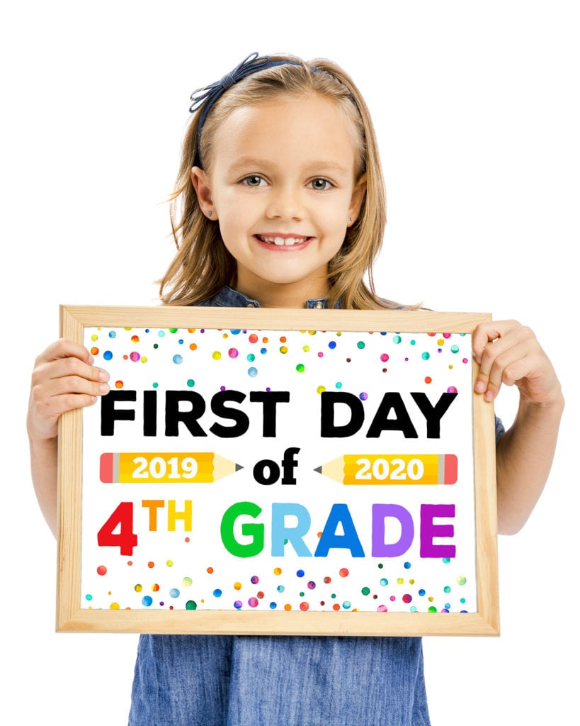 "Cute girl holding ""First Day of School"" sign with rainbow lettering"