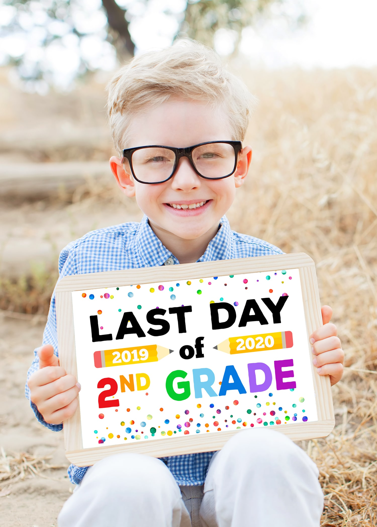 smart excited little boy in glasses holding chalkboard ready for school, back to school concept