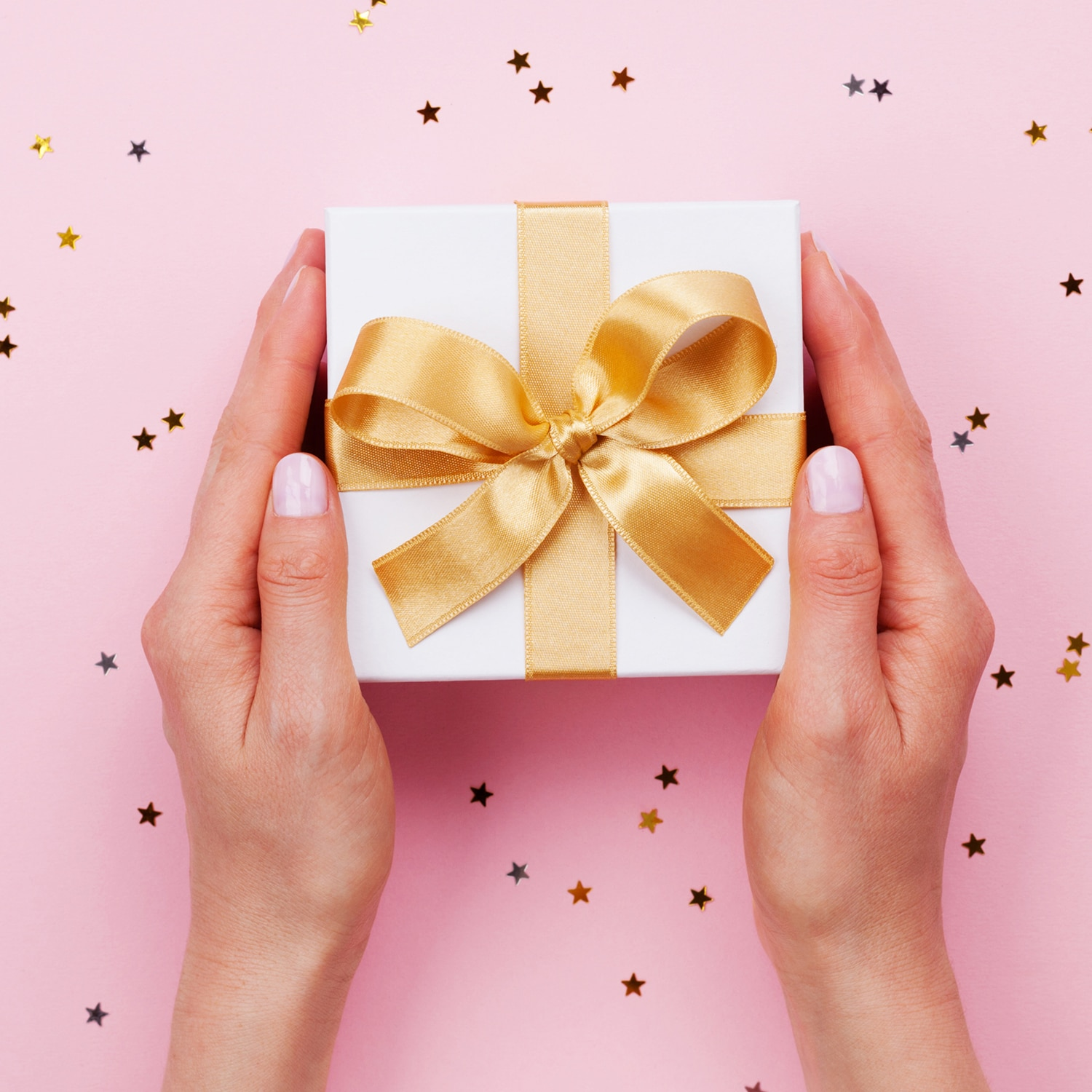 Womans hands holding gift or present box decorated confetti on p