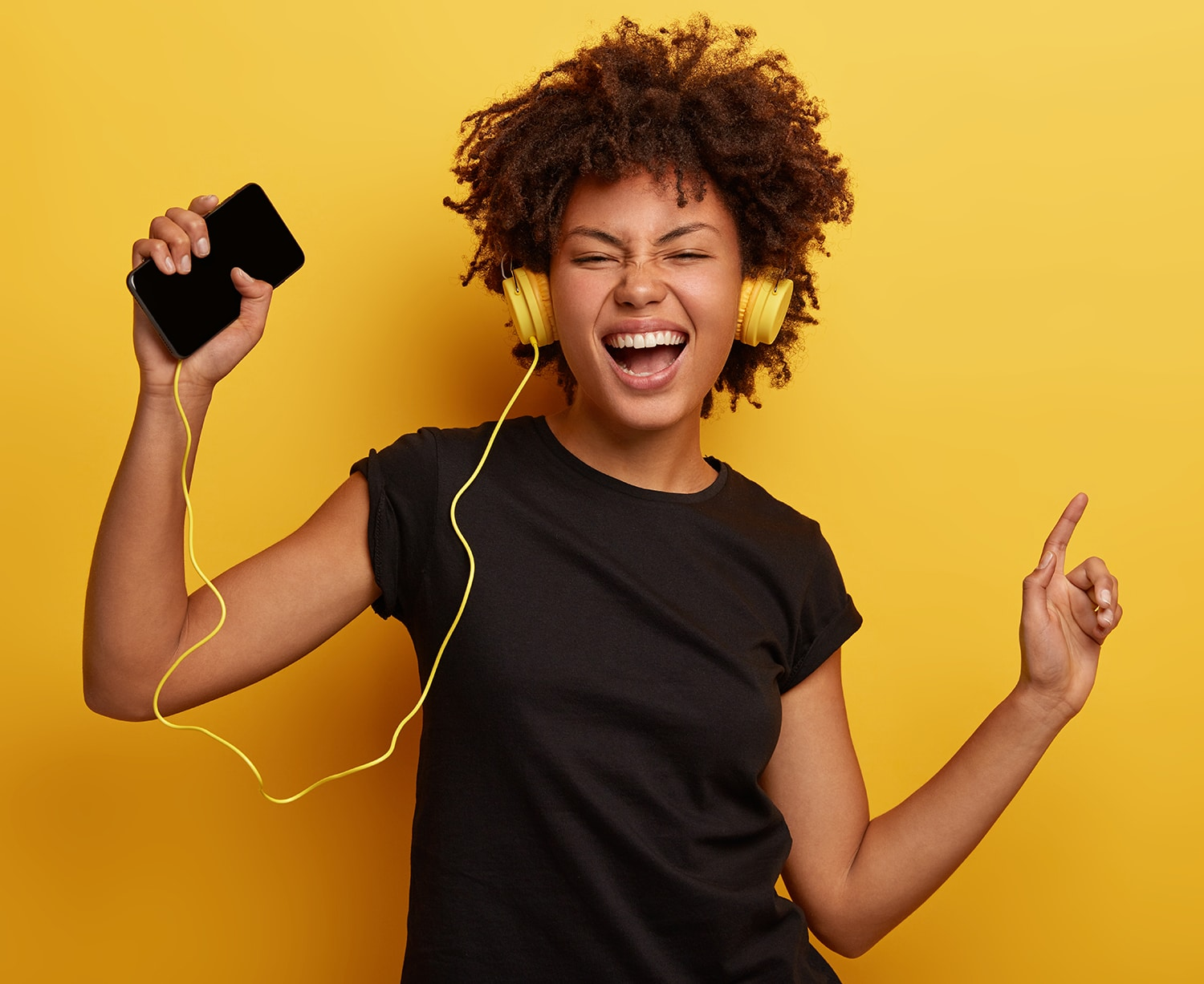 Girl listening to music with headphones on yellow background