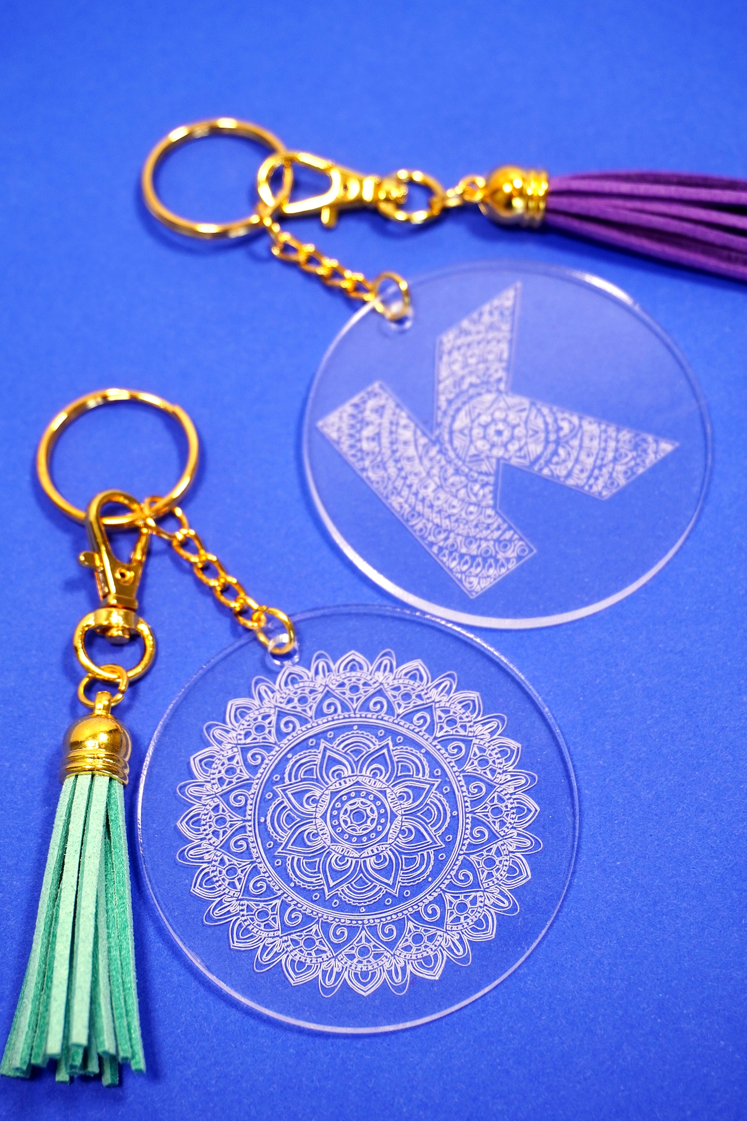 Mandala engraved acrylic keychains on a blue background made with Cricut Engraving Tip
