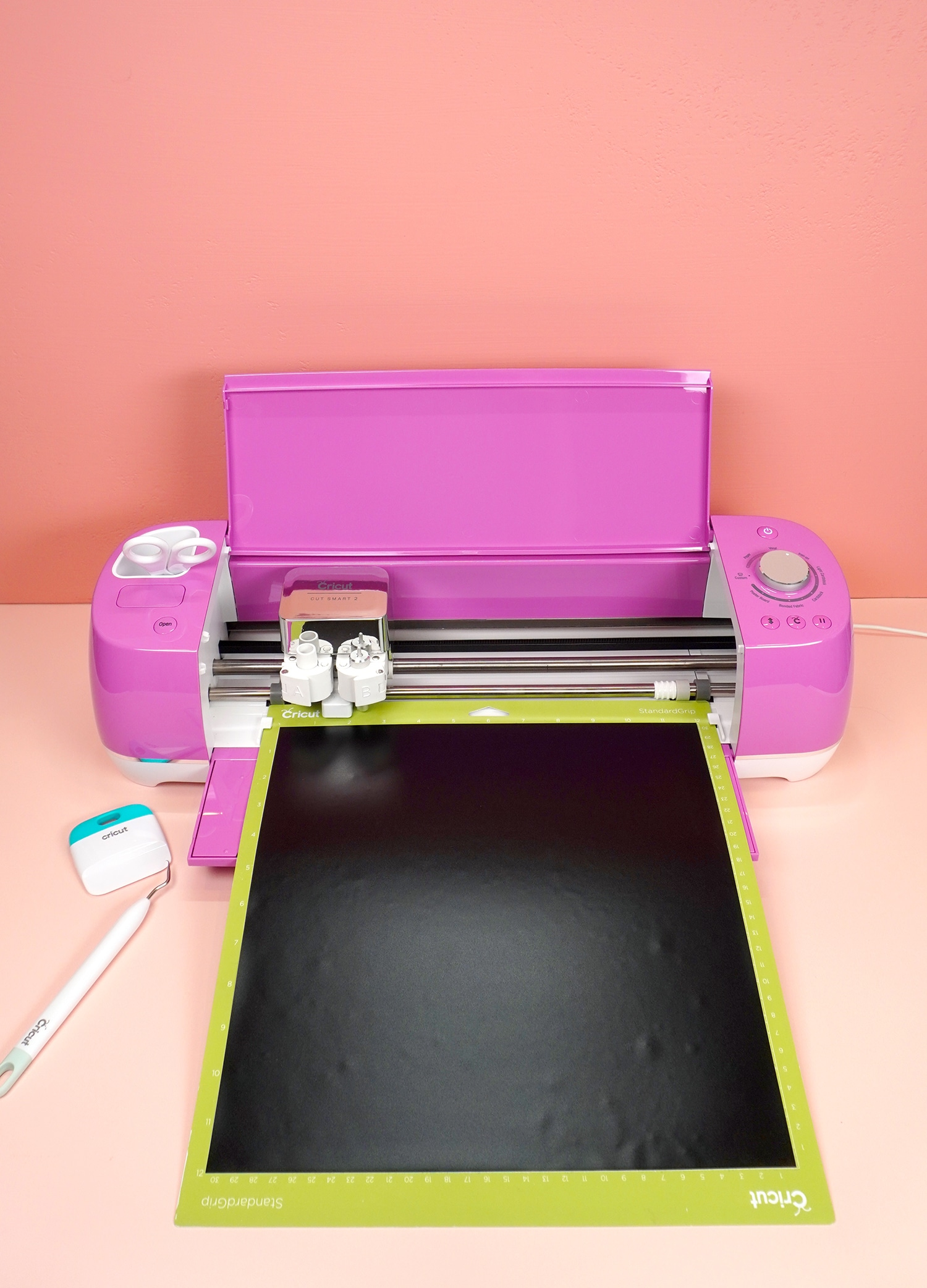 Fuchsia Cricut Explore Air 2 machine with mat and black vinyl, scraper tool, and weeding hook