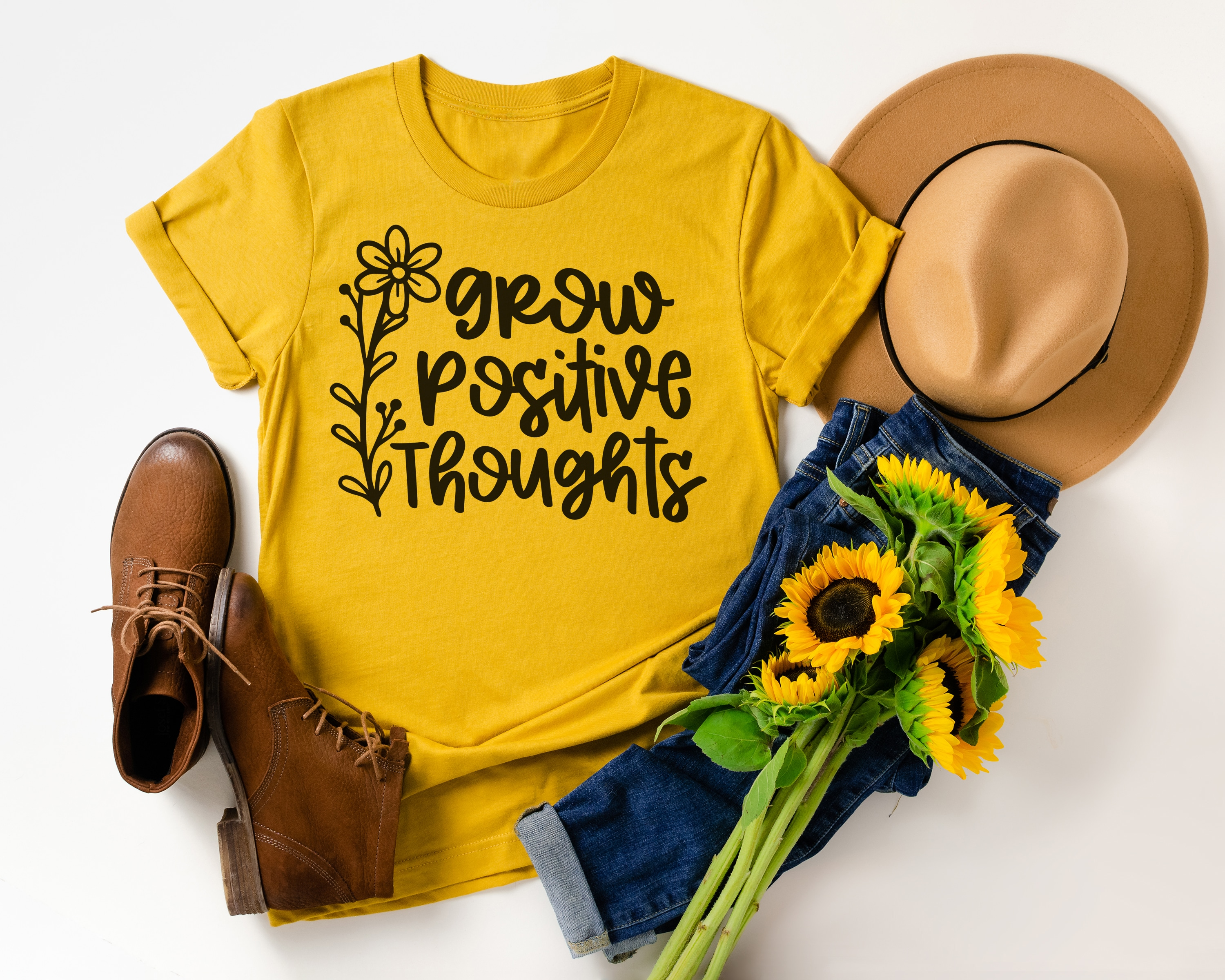 """Grow Positive Thoughts"" on mustard yellow shirt with styled outfit, hat, and sunflowers"