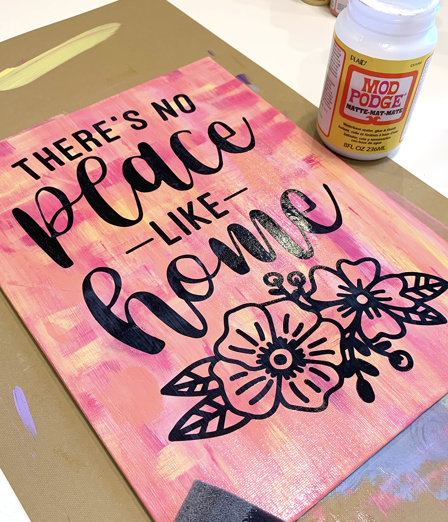 Applying Mod Podge to a hot mess canvas with vinyl quote