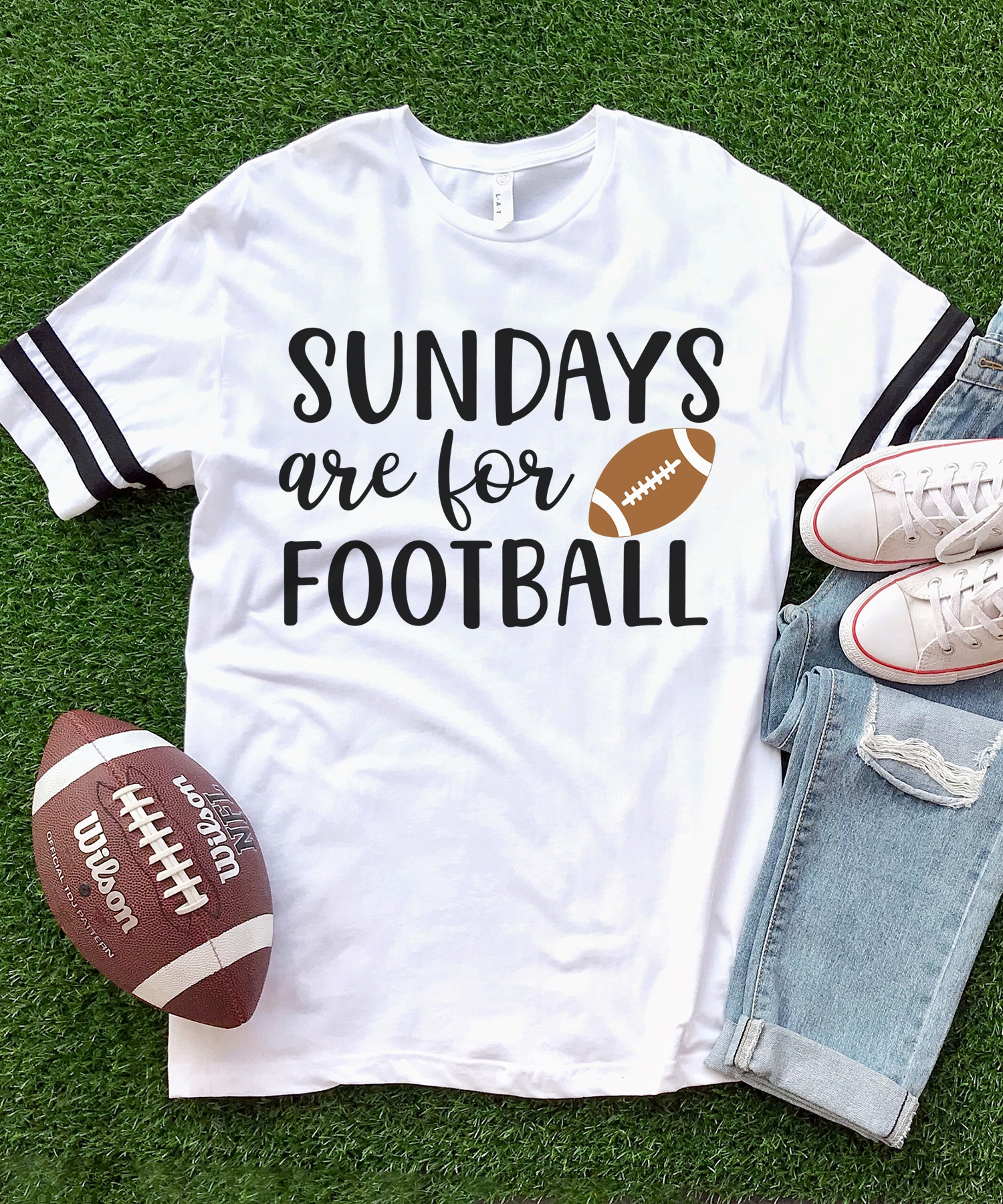 "White shirt with ""Sundays are for Football"" graphic on a grass turf background with jeans, shoes, and a football"