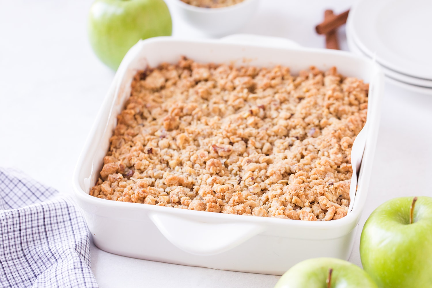 White baking dish with apple pie bars and streusel topping with apples on the side