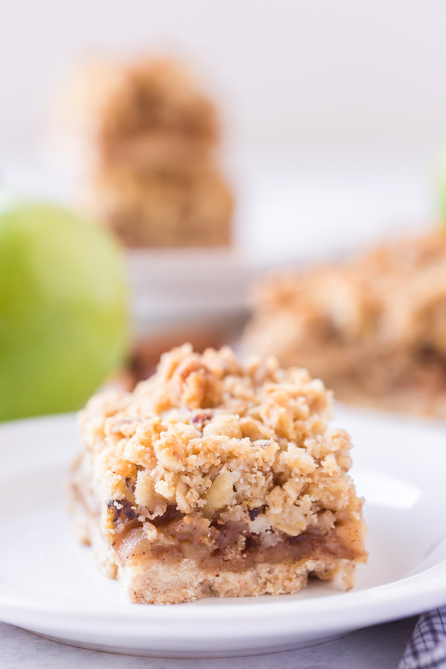 Apple pie bar on white plate with apples and more bars in the background