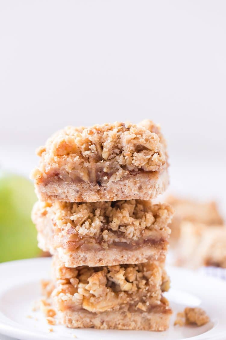 Three Apple Pie Bars stacked on a white plate with green apples in the background