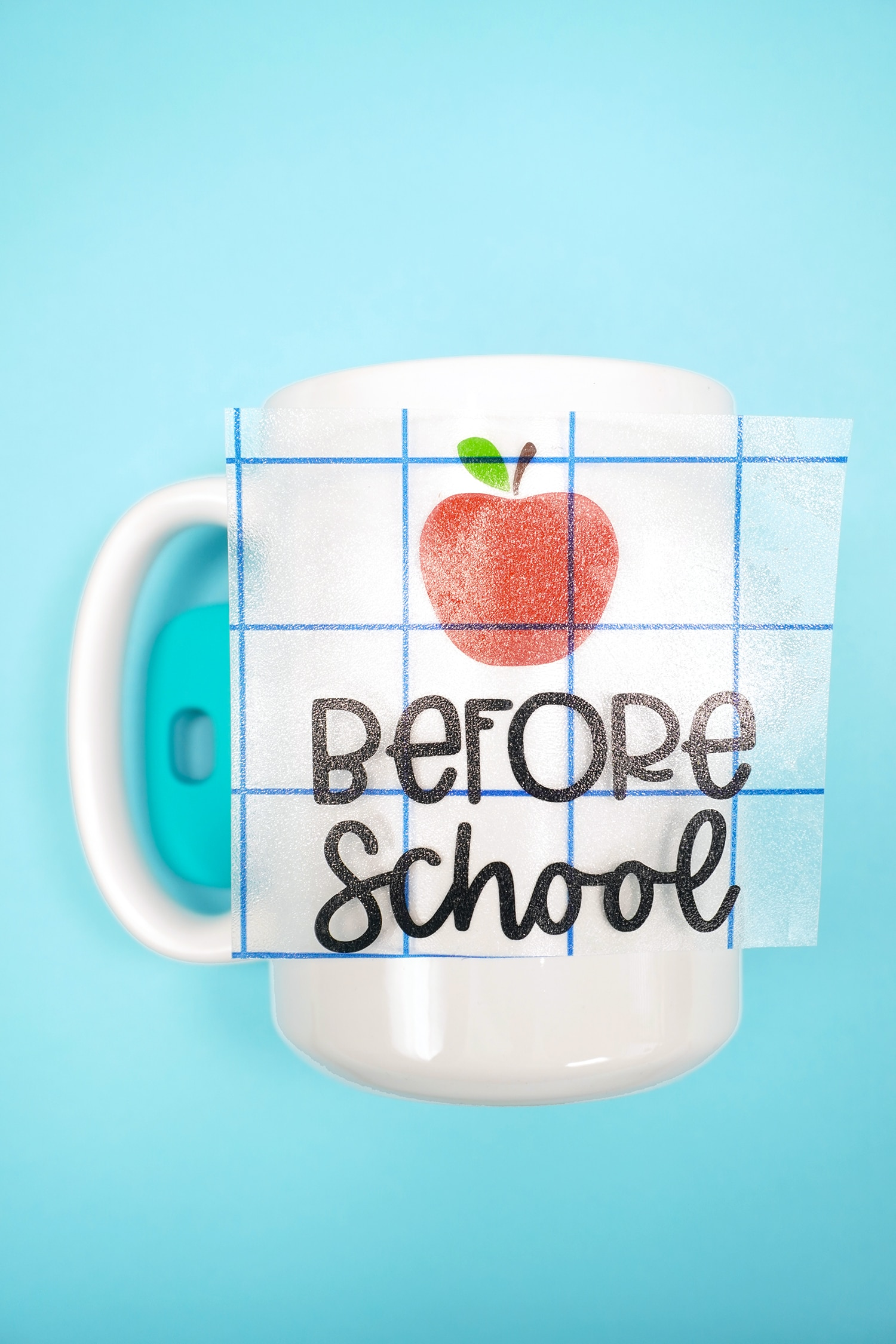 """Before School"" and apple vinyl designs on transfer tape in the process of being applied to a white mug"