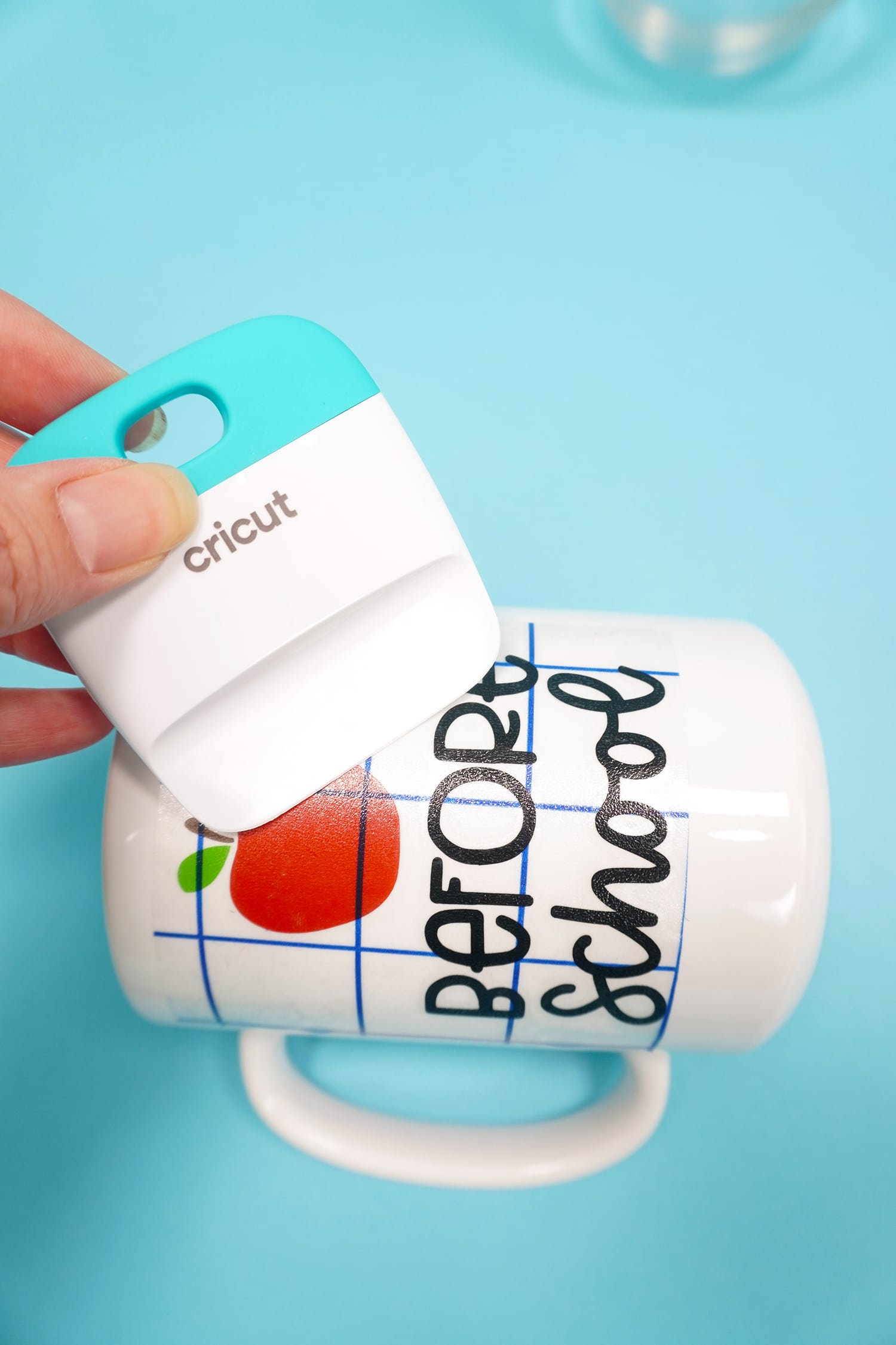 "Using a scraping tool to apply an apple and ""before school"" design to a white mug"