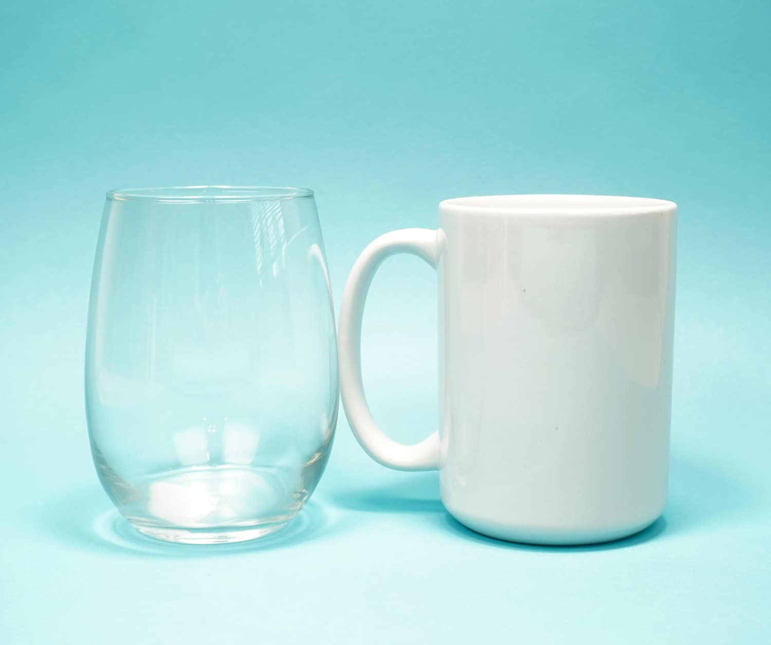 Clear stemless wine glass and white mug on light blue background