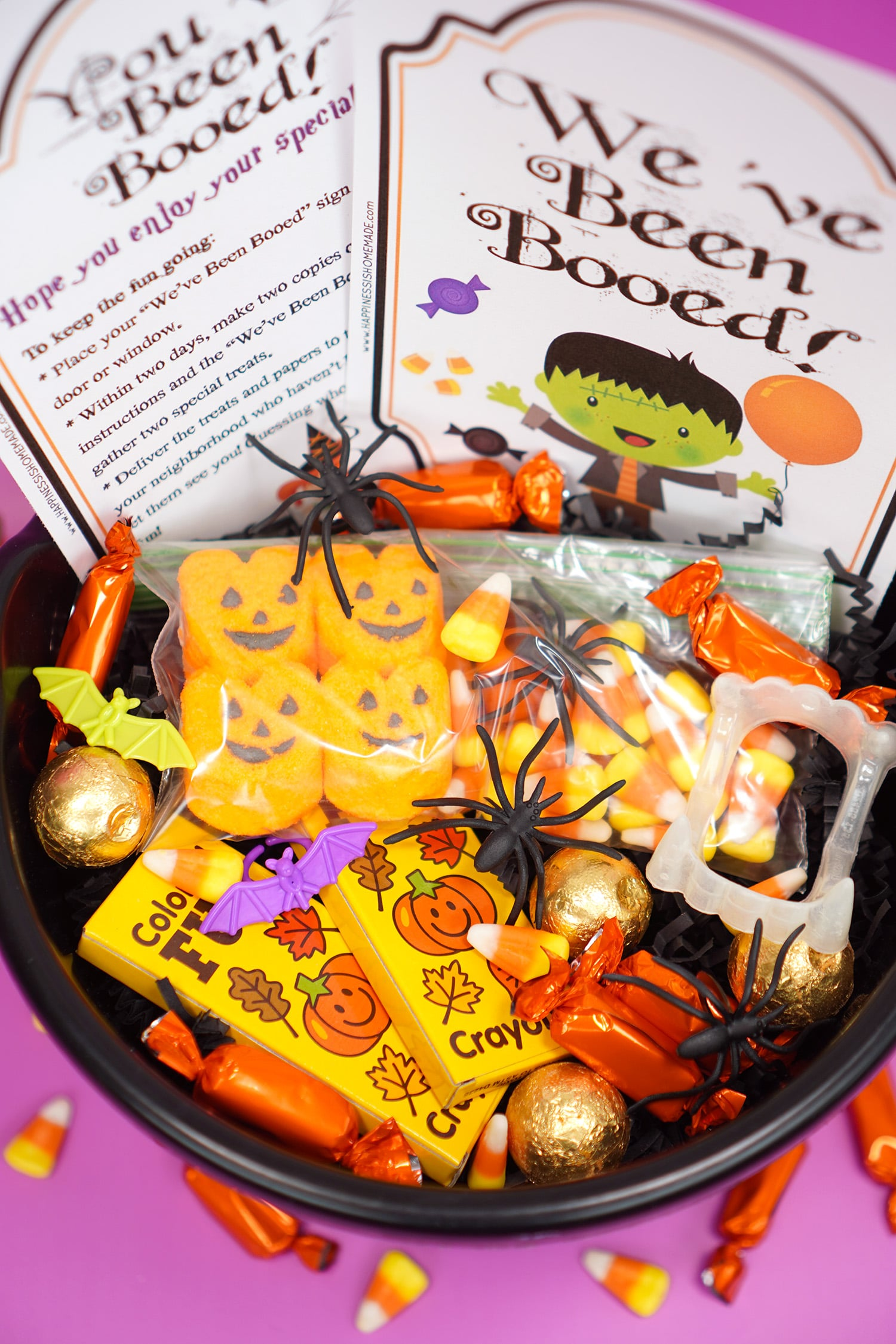 "Booed printables and Boo Basket filled with Hallowen candy and novelty toys with ""You've Been Booed""and "" We've Been Booed"" printable signs on purple background"