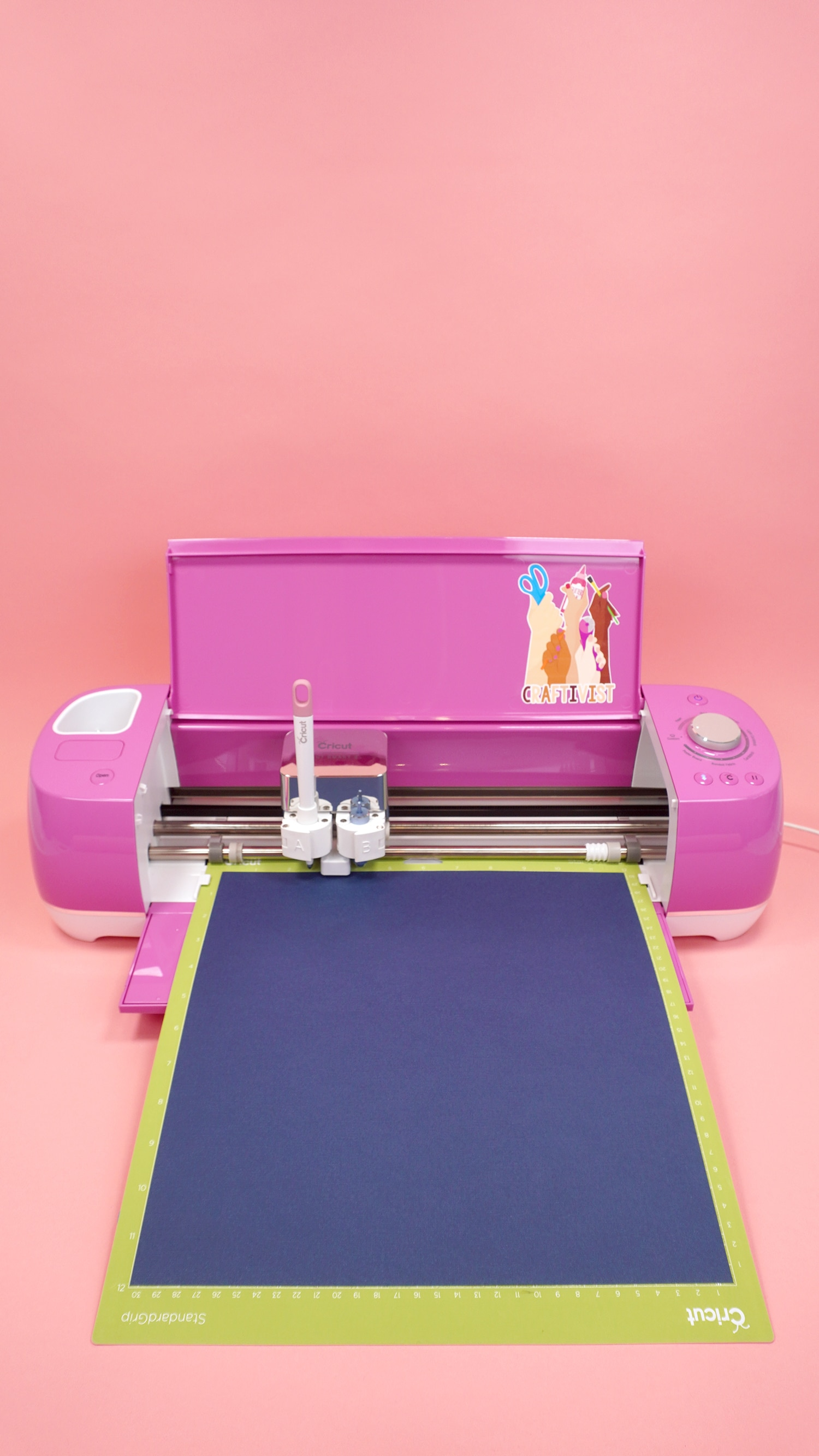Navy cardstock on mat in pink Cricut Explore Air 2 on coral background