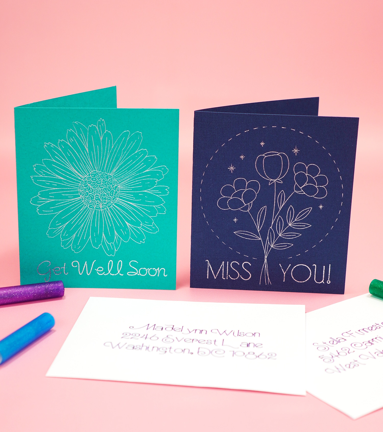 Silver foiled cards on pink background with envelopes