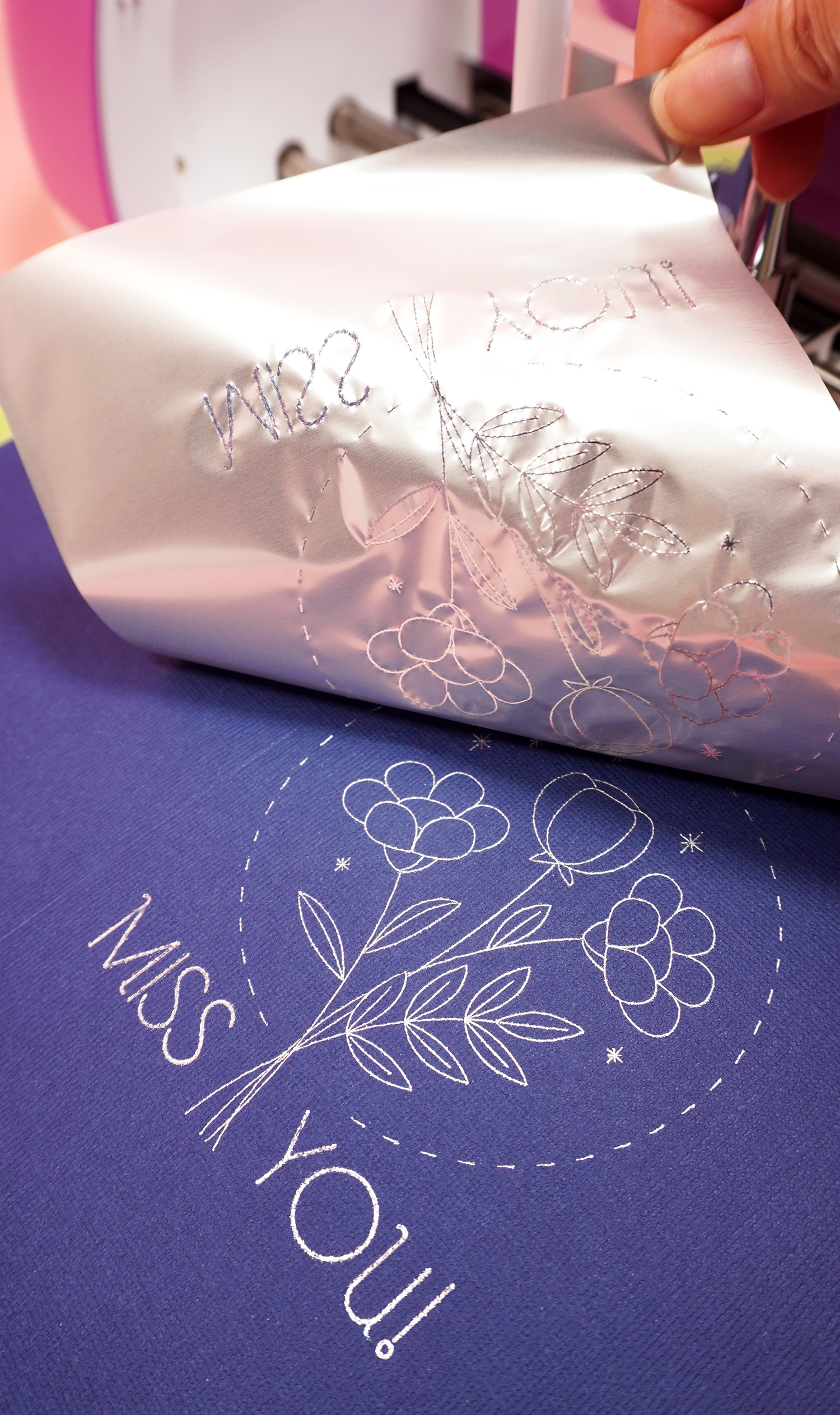 """Peeling back silver foil sheet to reveal """"Miss You"""" and flower bouquet foil design on navy blue card"""