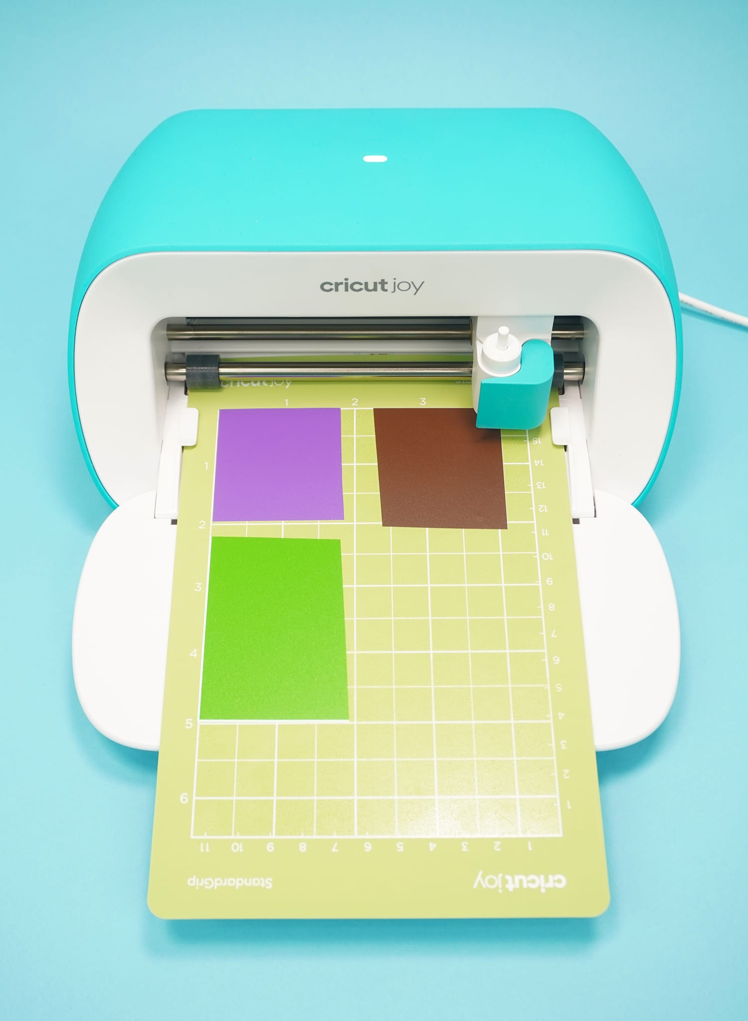 Cricut Joy machine with green cutting mat and scraps of purple, brown, and green vinyl