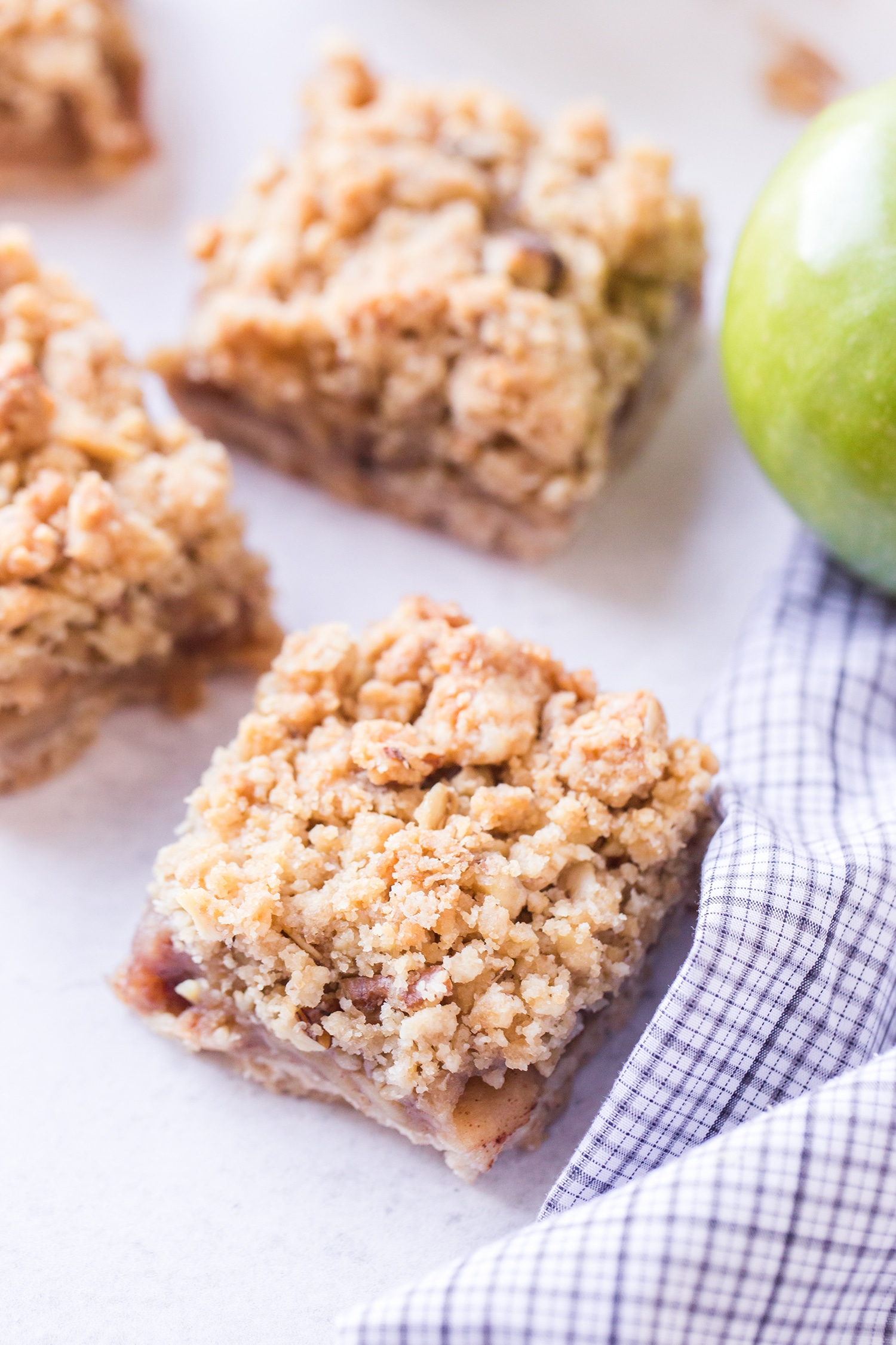 Cut apple pie bars with green apple in background