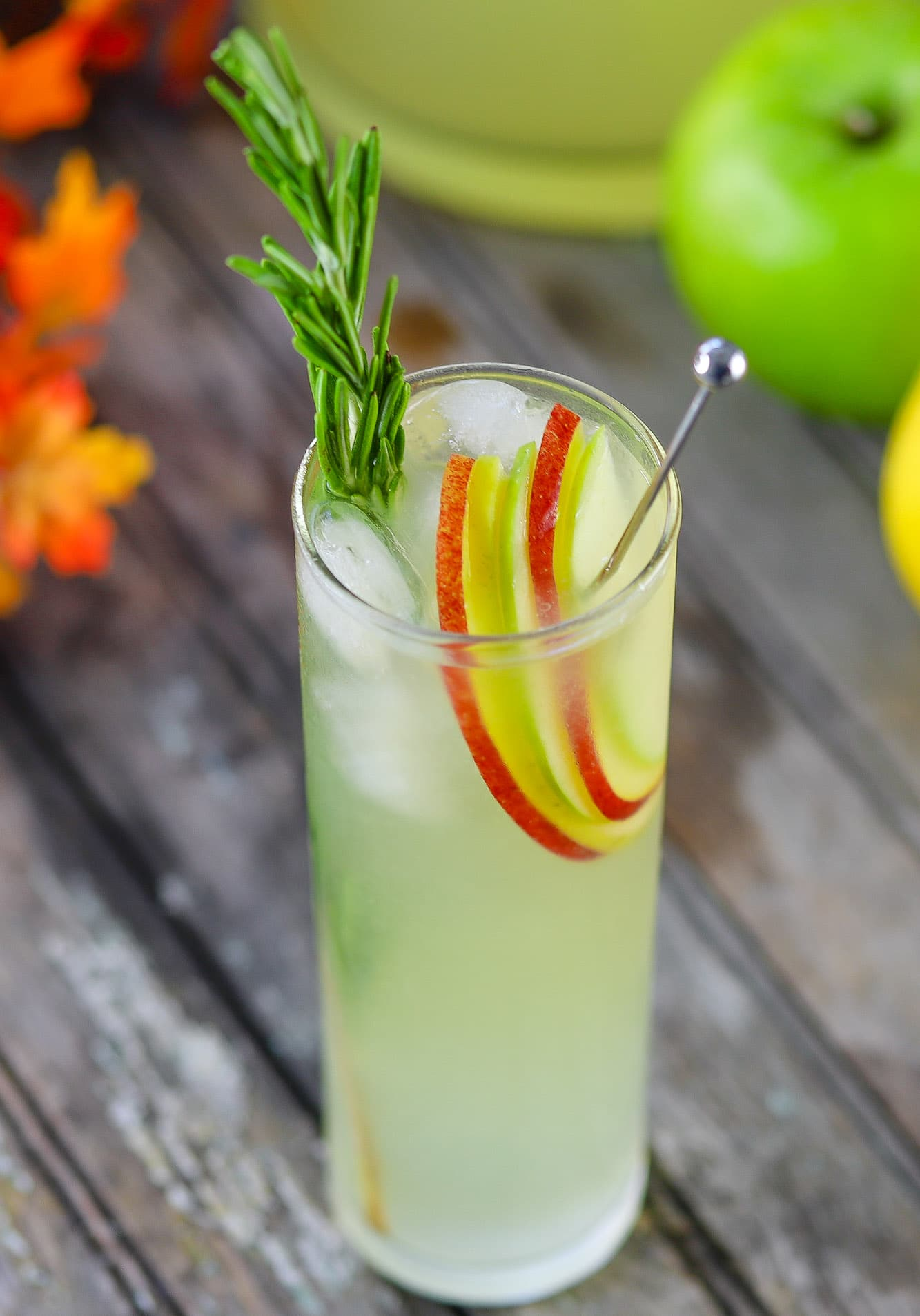 Hard lemonade in glass garnished with apple slices and a sprig of rosemary