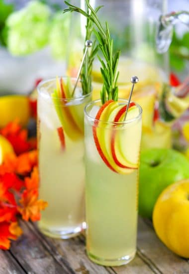 Two tall glasses of hard lemonade garnished with apple slices and a sprig of rosemary