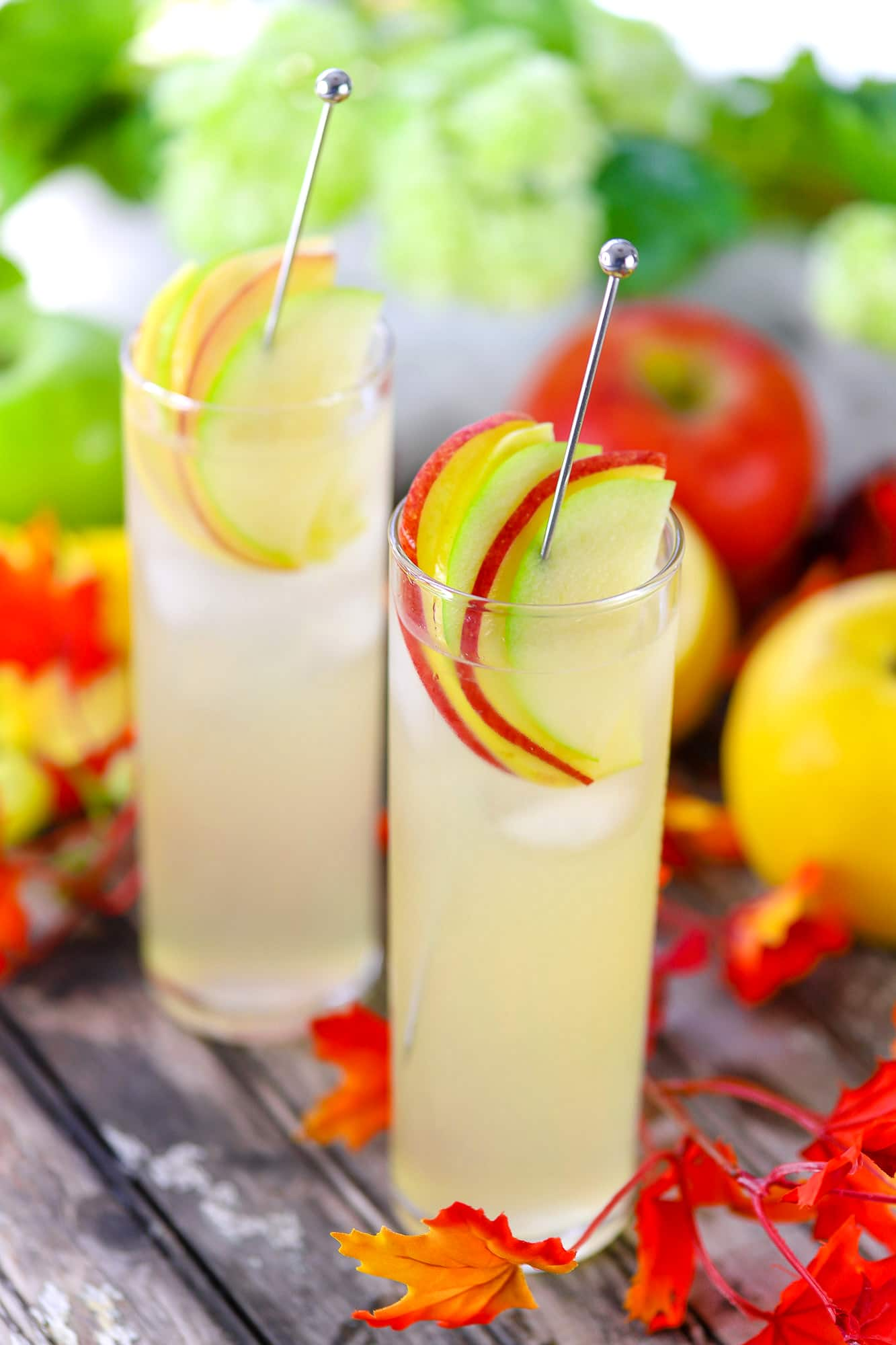 Two tall glasses of hard lemonade garnished with red, green, and yellow apple slices