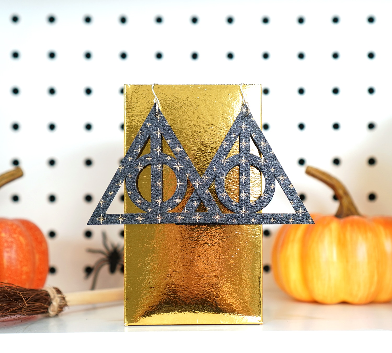 Deathly Hallows leather earrings with gold star pattern hanging on gold box with pumpkin in background
