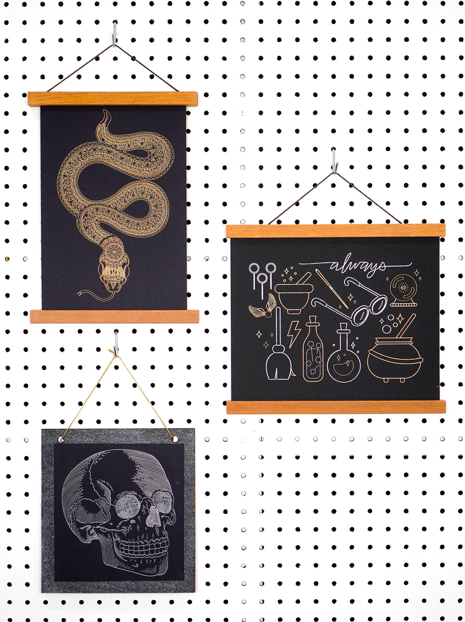 Gold and silver foil art prints (snake, skull, and wizardry) hanging on white pegboard