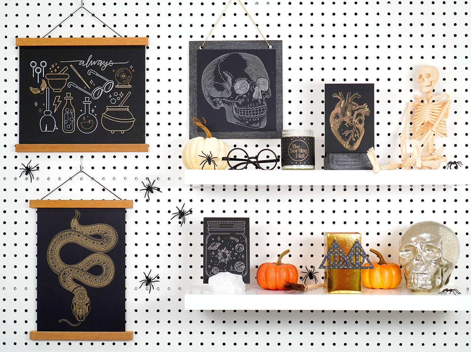 Foil Halloween art prints and Halloween Decorations on white shelves and pegboard