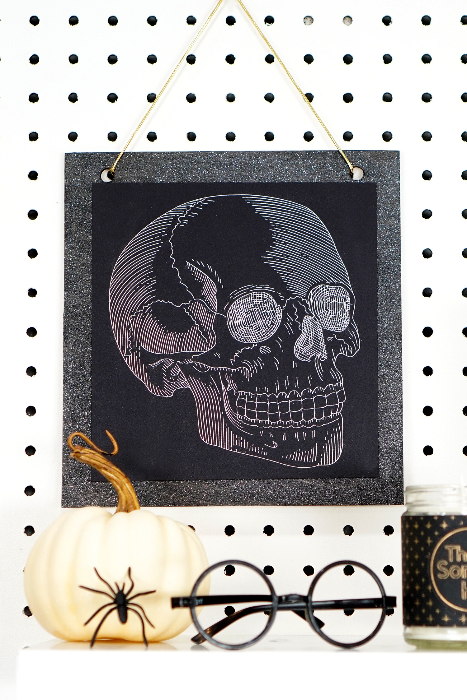 Silver foil skull art print hanging on pegboard with pumpkin, spider, and Harry Potter glasses in foreground