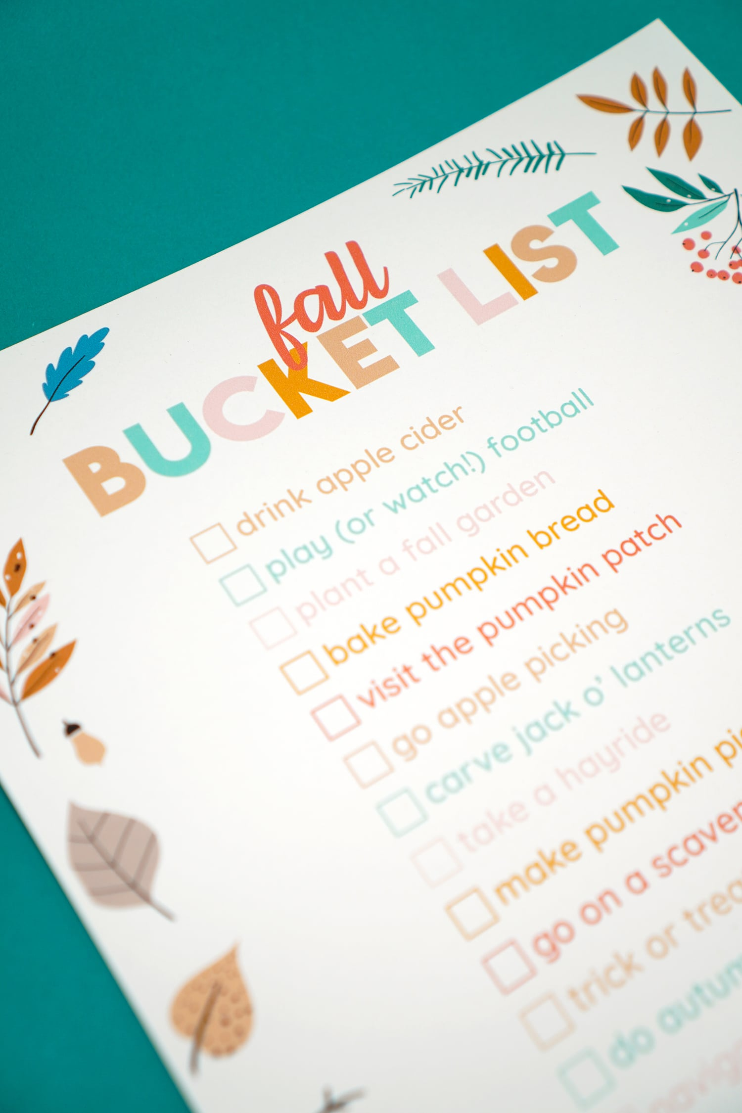 close up of printable fall bucket list on teal background