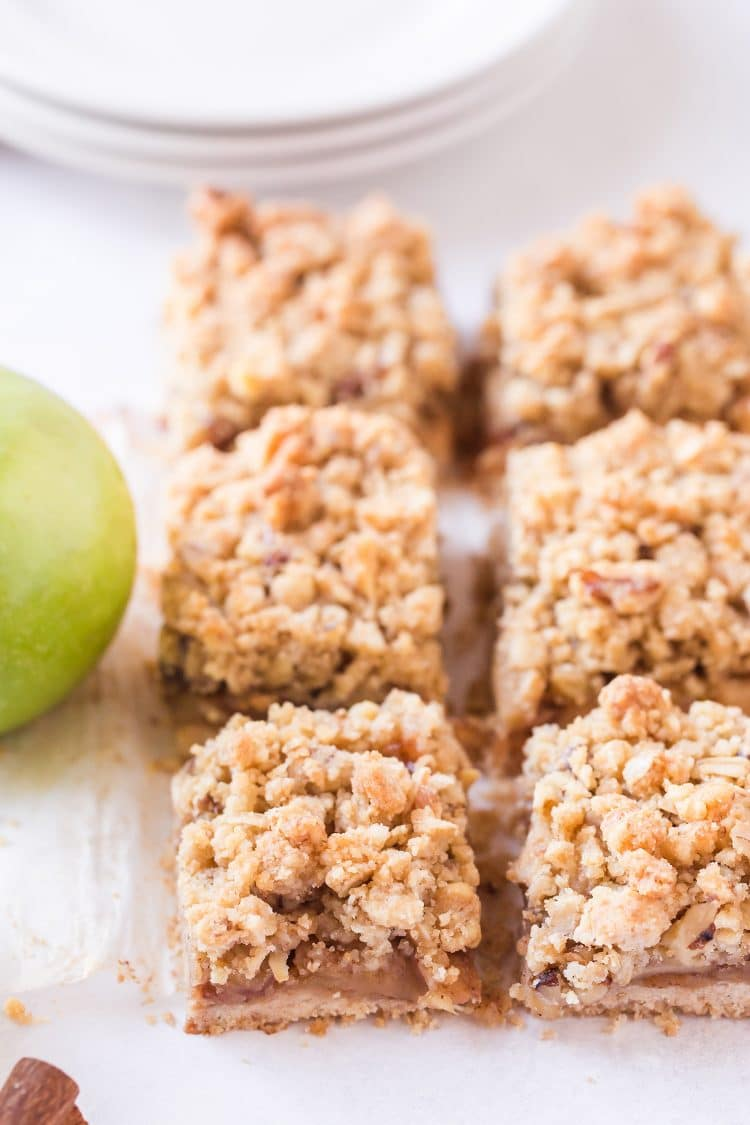 Sliced apple pie bars with green apple in background