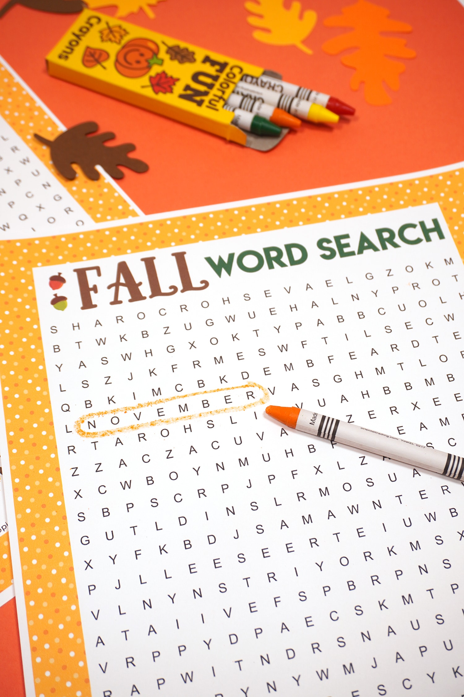 "Fall Word Search Printable with ""November"" circled on dark orange background with orange crayon and paper leaves"