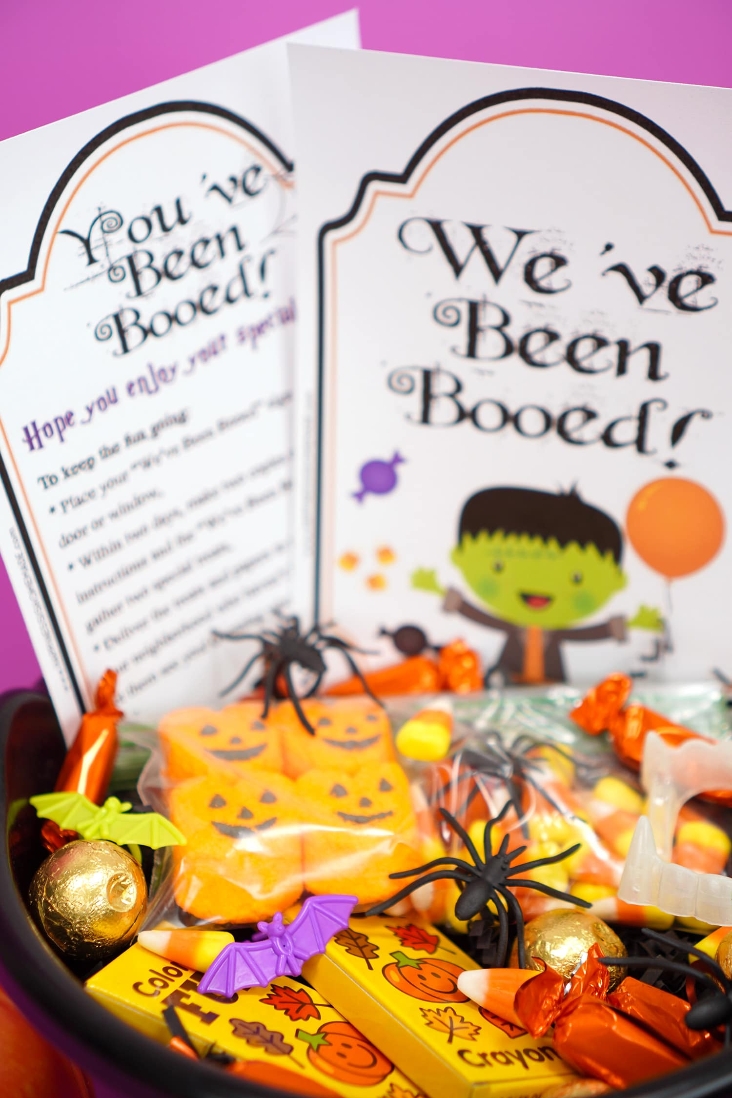 "Boo Basket filled with Hallowen candy and novelty toys with ""You've Been Booed""and "" We've Been Booed"" printable signs"