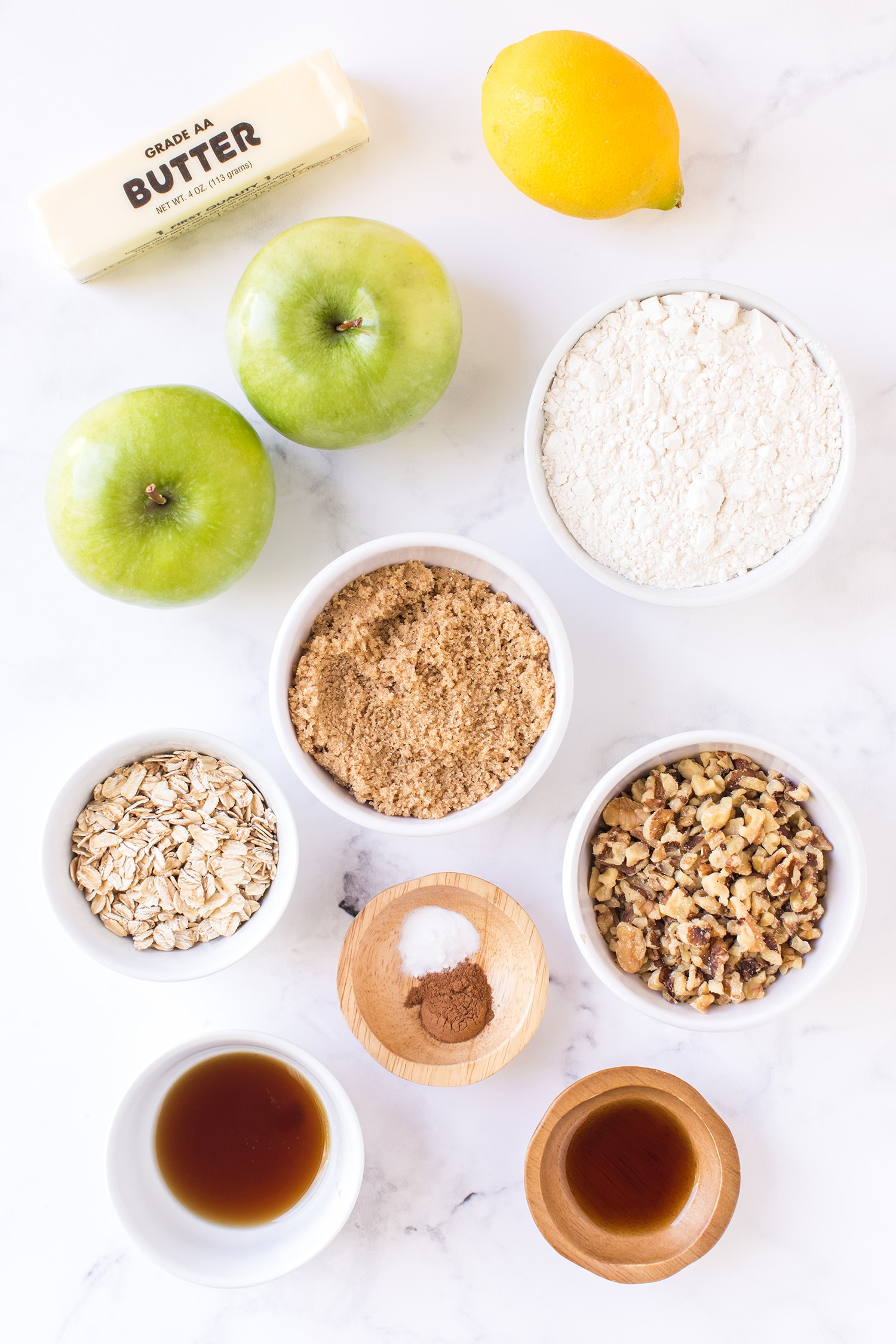 Ingredients for Apple Pie Bars in small bowls on white marble background