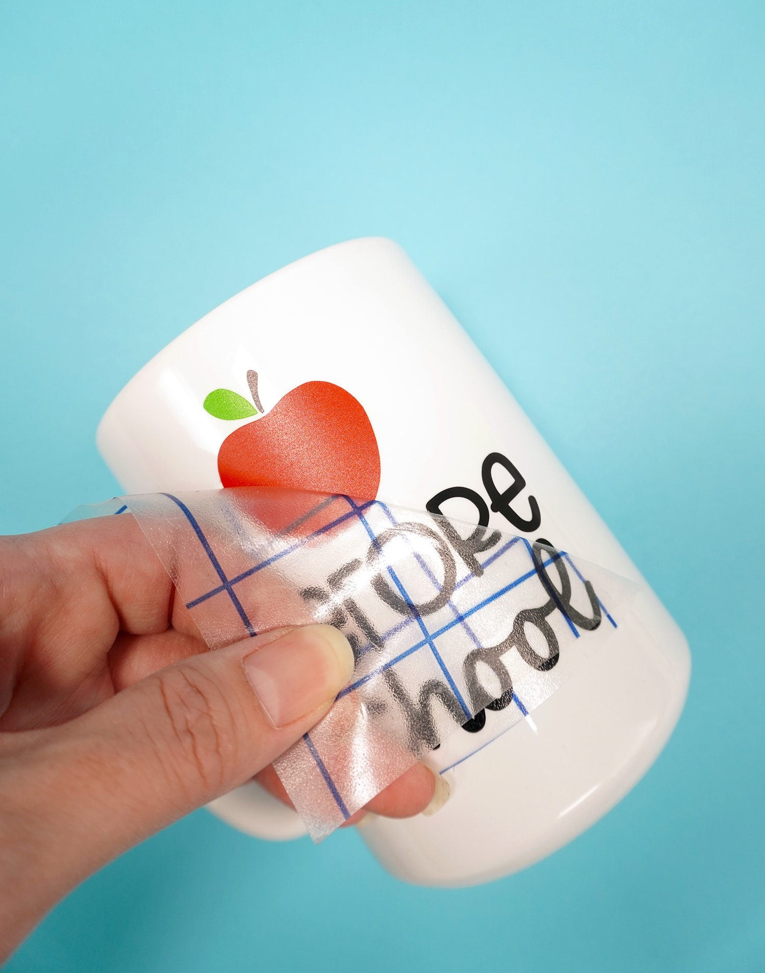 White mug on blue background - peeling transfer tape to reveal apple design