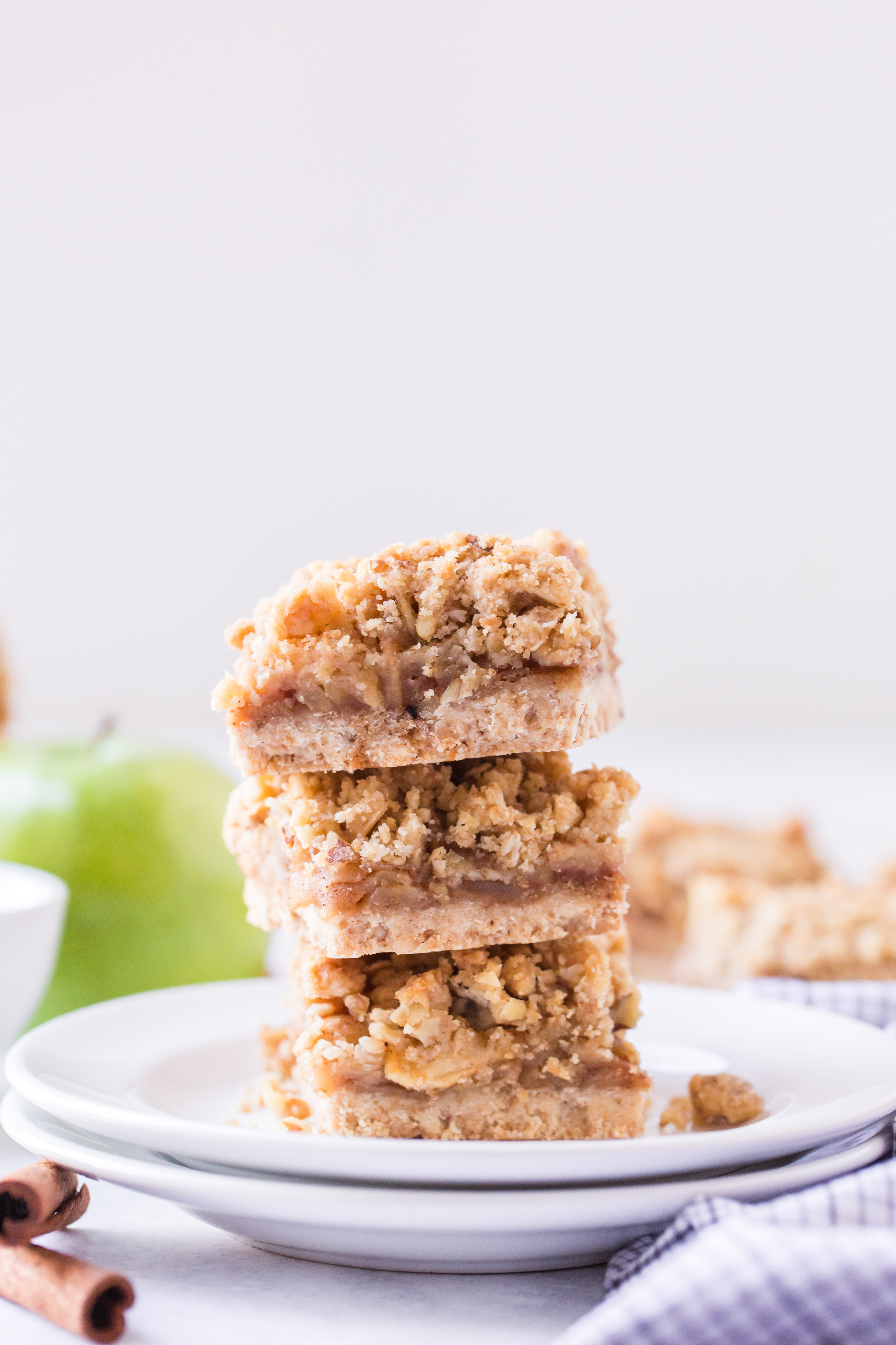 Three stacked apple pie bars with green apples and cinnamon sticks in background