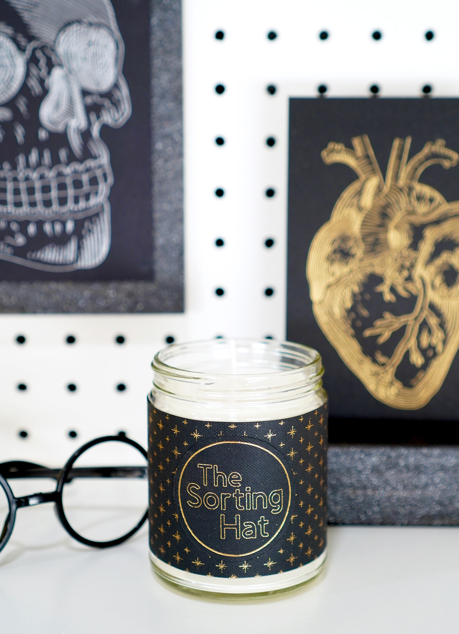 """The Sorting Hat"" candle with black label with gold stars with Harry Potter glasses, foil skull and anatomical heart prints in background"