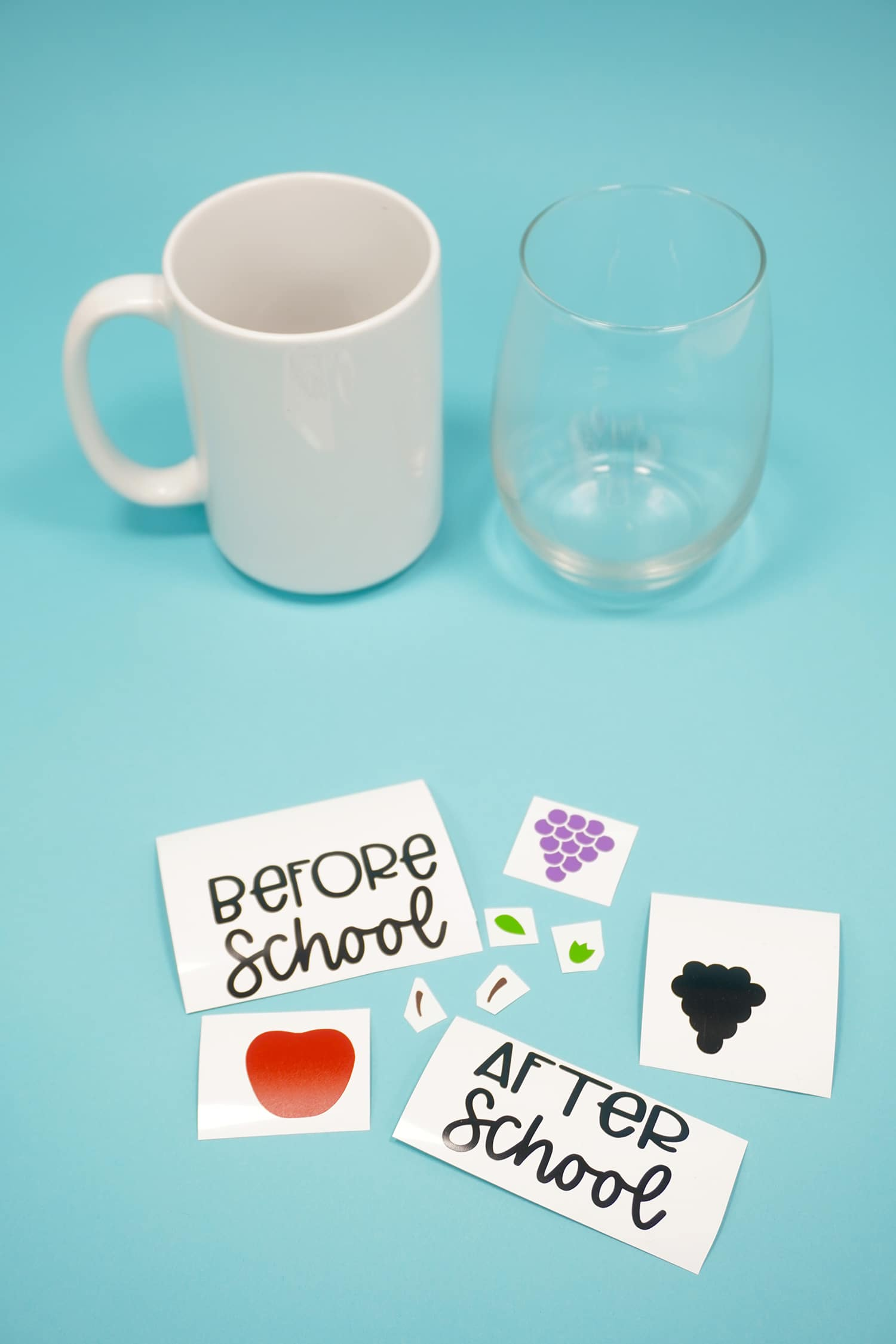 White mug and clear wine glass on blue background with assorted vinyl designs in foreground