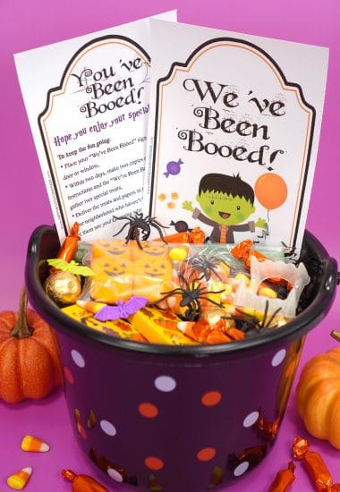 "Boo Basket filled with Hallowen candy and novelty toys with ""You've Been Booed""and "" We've Been Booed"" printable signs on purple background with pumpkins"