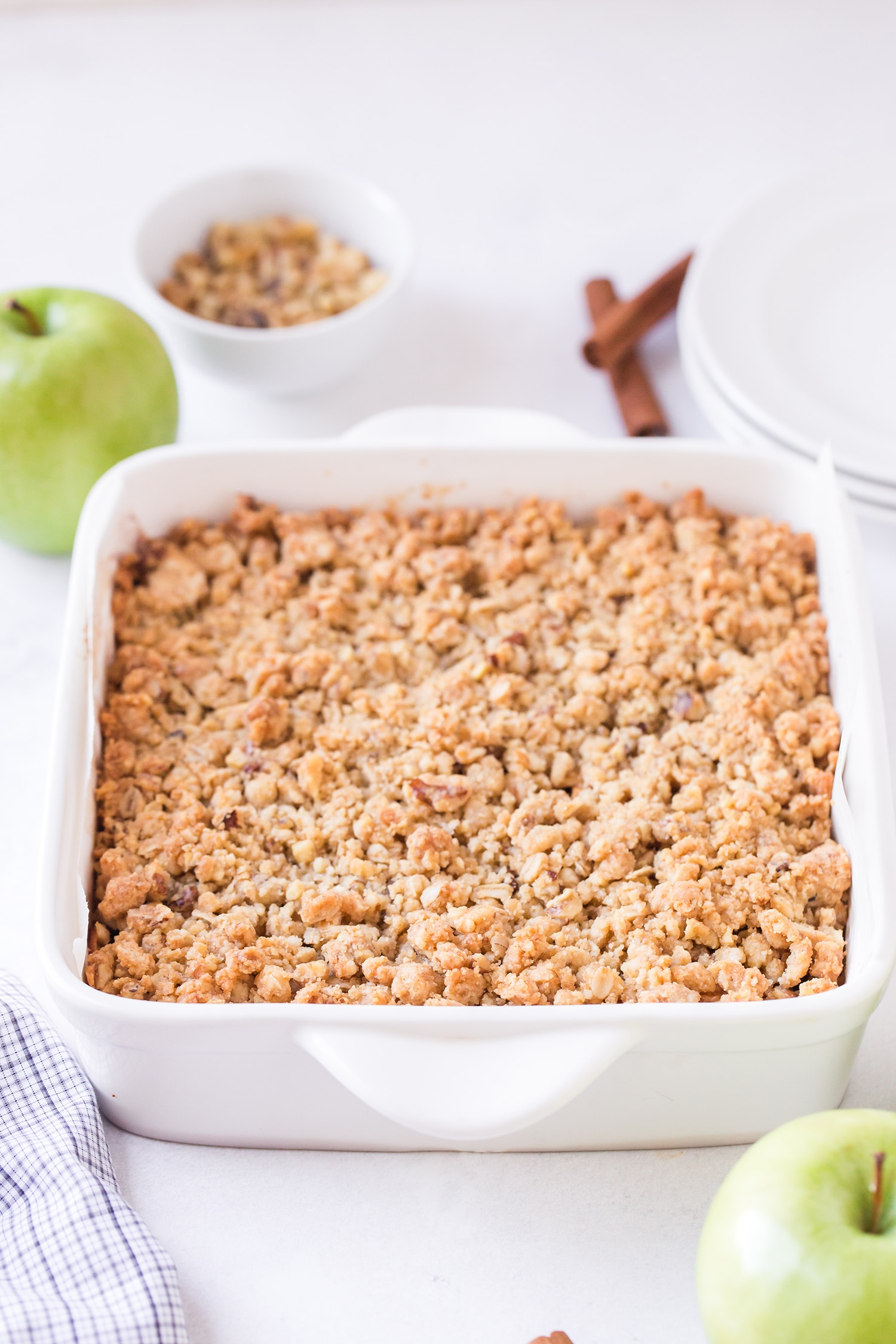 Yummy Apple Pie Bars in a white baking dish with apples and cinnamon sticks in background