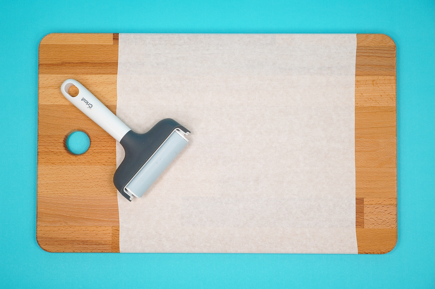 Cutting board with masking and a brayer on aqua background