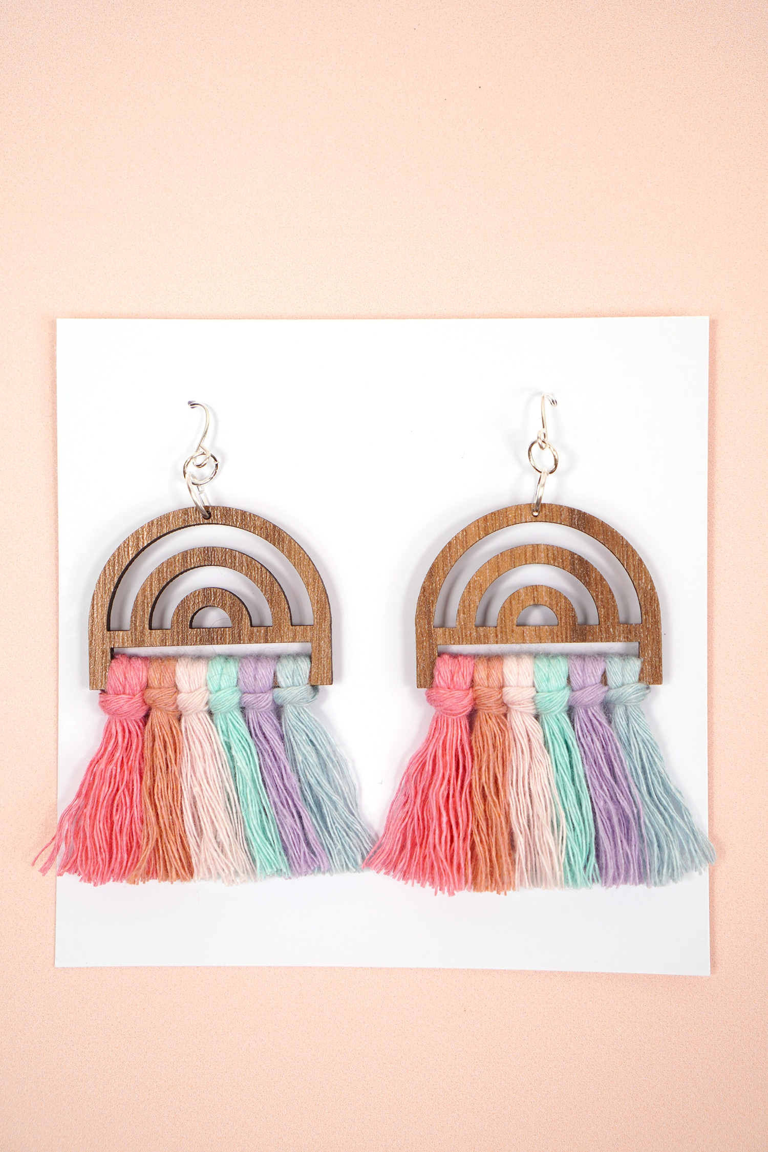 colorful wooden rainbow macrame earrings on white jewelry card on peach background
