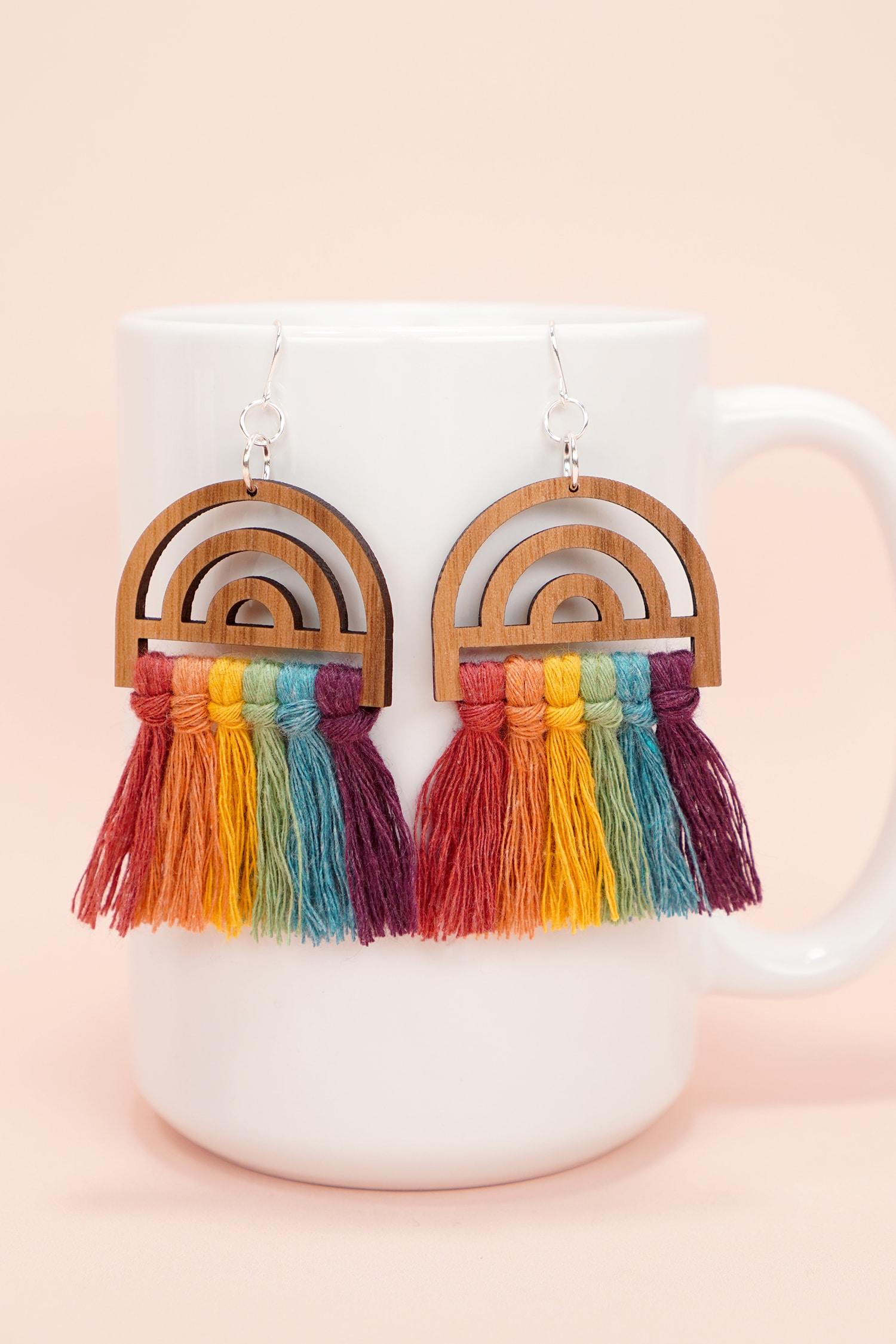 colorful wooden rainbow macrame earrings on white mug on peach background