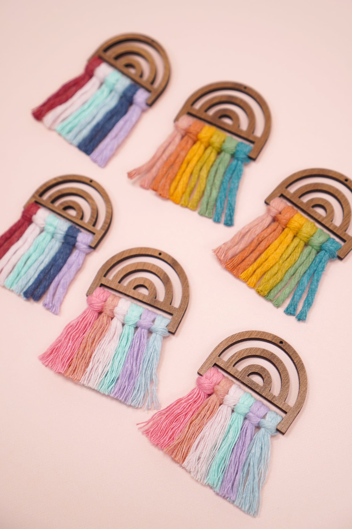 close up of different pairs of rainbow macrame earrings on peach background