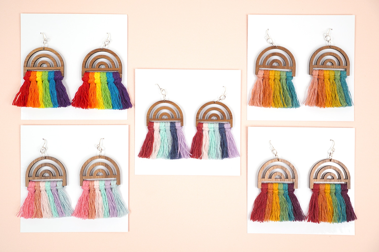 5 pairs of rainbow macrame earrings on white jewelry cards on peach background